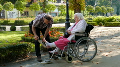 Caregiver is helping senior lady in a wheelchair Stock Footage