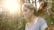 Fair-skinned blond woman jogging in the forest to keep fit Stock Footage