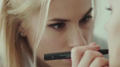 Makeup artist paints lips of a beautiful girl. Model with lipstick Stock Footage