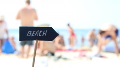 Beach sign - tourists and umbrellas on summer hot day and tropical sea Stock Footage
