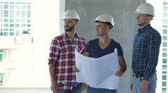 Three builders pose at the building under construction Stock Footage