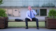 Happy businessman talking on the phone sitting on a bench in the street Stock Footage