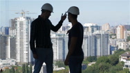 Two builders look at the landscape of high buildings Stock Footage