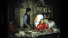 1974: family gathering at table, while grandmother reaches up on high shelf  Stock Footage