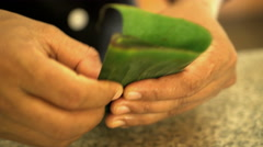Hands folding healthy low calorie banana leaves in preparation of Asian Vegan Stock Footage