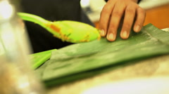 Balinese chef wrapping Basa Gede in healthy low cholesterol banana leaves in Stock Footage
