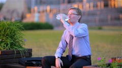 Businessman is thirsty and drinks water from a bottle Stock Footage
