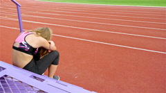Girl athlete taking breath exhausted disappointed after running on stadium Stock Footage