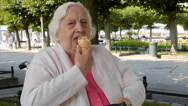 Senior woman in a wheelchair eats ice cream in a park Stock Footage