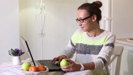 Woman eating fruit while working on computer in office Stock Footage