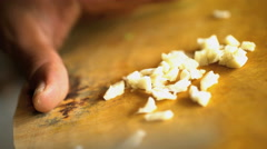 Balinese chef in restaurant kitchen cutting nutritious raw garlic on wooden Stock Footage