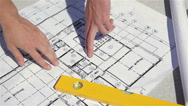 Male fingers point at the plan of the building construction Stock Footage