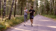 Attractive woman and handsome man jogging in green forest in the morning Stock Footage