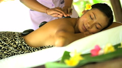 Luxury hot stone massage treatment by professional masseuse on young Asian Stock Footage