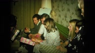1974: people on couch exchanging and opening christmas gifts FORT WAYNE, INDIANA Stock Footage