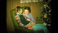 1974: couple is sitting next to christmas tree FORT WAYNE, INDIANA Stock Footage