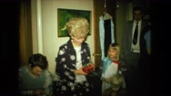 1974: woman holding red present surrounded by her family on christmas.  Stock Footage