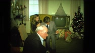 1974: christmas tree is seen with child opening presents FORT WAYNE, INDIANA Stock Footage