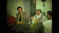 1974: older woman opening up wrapped gift as she is watched by family  Stock Footage