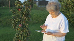 Old woman 80s holding a digital tablet outdoors Stock Footage