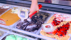 Sales of ice cream. Woman pulls balls of ice cream from refrigerator Stock Footage