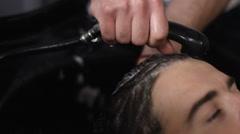 Man Barber Washing Male Hair in a Barbershop Stock Footage