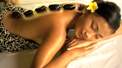 Relaxing hot stone treatment on young Asian female client on holiday at Balinese Stock Footage