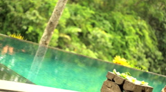 Young Asian female in sarong relaxing on chair drinking fresh juice by infinity Stock Footage