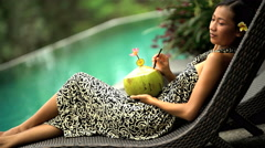 Young ethnic girl in sarong relaxing on chair drinking refreshing coconut by Stock Footage