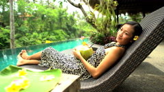 Beautiful ethnic female in sarong drinking low fat natural coconut juice by Stock Footage