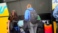 Students taking bags and luggage off the bus in front of the university campus Stock Footage