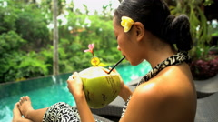 Beautiful young Asian girl in sarong relaxing with fresh healthy coconut juice Stock Footage