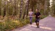 Young couple enjoying their run in the forest Stock Footage