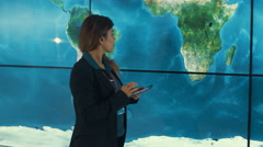 4K Businesswoman with tablet looking at large world map graphic on video wall Stock Footage