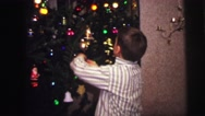1973: boys hanging christmas ornaments in their pajamas LYNBROOK, NEW YORK Stock Footage