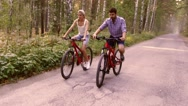 Young attractive couple starts to move on bicycles in summer park Stock Footage