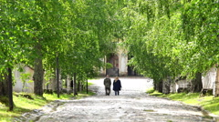 People walk on the stone pavement under the curved arch Stock Footage