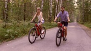 Young woman and handsome man cycling happily together Stock Footage