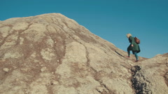 Young woman climbing the hill in the desert and raises her hands up Stock Footage