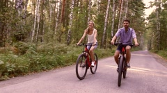 Portrait of happy couple having fun on bicycle ride in the summer park Stock Footage