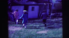 1973: children playing in backyard all dressed up and seeming to be getting Stock Footage
