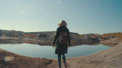 Young woman coming up to the lake in the desert and admires the view Stock Footage