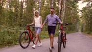 Happy couple walking with their bicycles in the forest Stock Footage