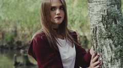 Portrait of beautiful girl in nature. Model posing near the tree Stock Footage
