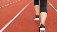 Steadicam shot of a teenager girl athlete legs running on a stadium track Stock Footage