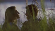 Close-up of kissing couple sitting in tall grass Stock Footage