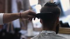 A British London barber using a scissors to cut a mans hair Stock Footage