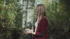 Beautiful girl in a burgundy cardigan lonely walks in the woods Stock Footage