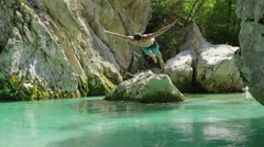 CLOSE UP: Cheerful man jumping head first into crystal clear water and swimming Stock Footage