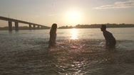 Young cheerful couple having fun in the water on a hot summer evening Stock Footage